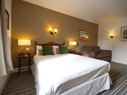 double bedroom with clean white sheets on bed at the innkeepers lodge at loch lomond