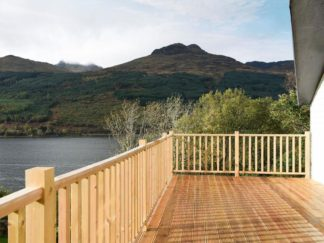 Lodge at Loch Lomond National Park overlooking water and mountains from large decking area