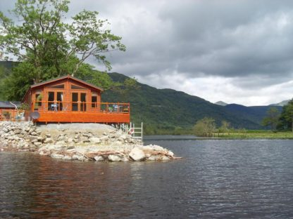 An Caisteal log cabin with water view and hills in background