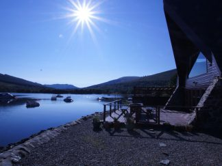 Lodge at Loch Lomond Looking over loch from decking with boats on water and blue sky and sunshine