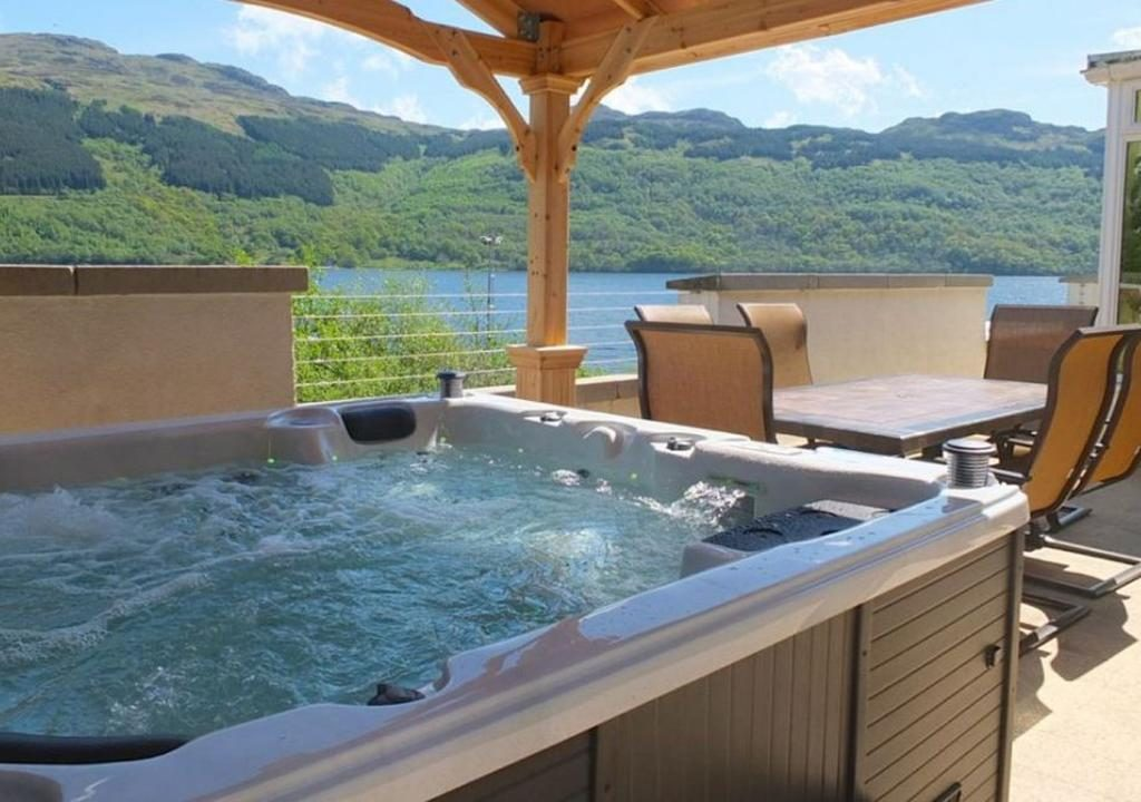 Hot tub and outdoor seating overlooking loch in sunshine